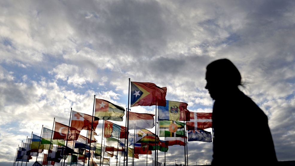 A woman walks by flags representing different nations outside the Coastal Cluster Olympic Village at the 2014 Winter Olympics, Saturday, Feb. 1, 2014, in Sochi, Russia. (AP Photo/David Goldman)