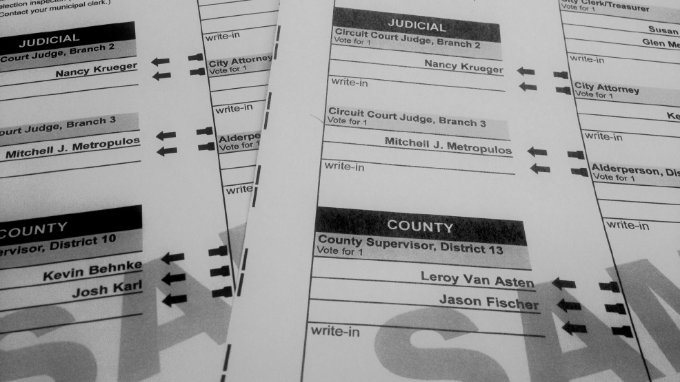 Two sample ballots with two different county board races is seen on April 2, 2014.