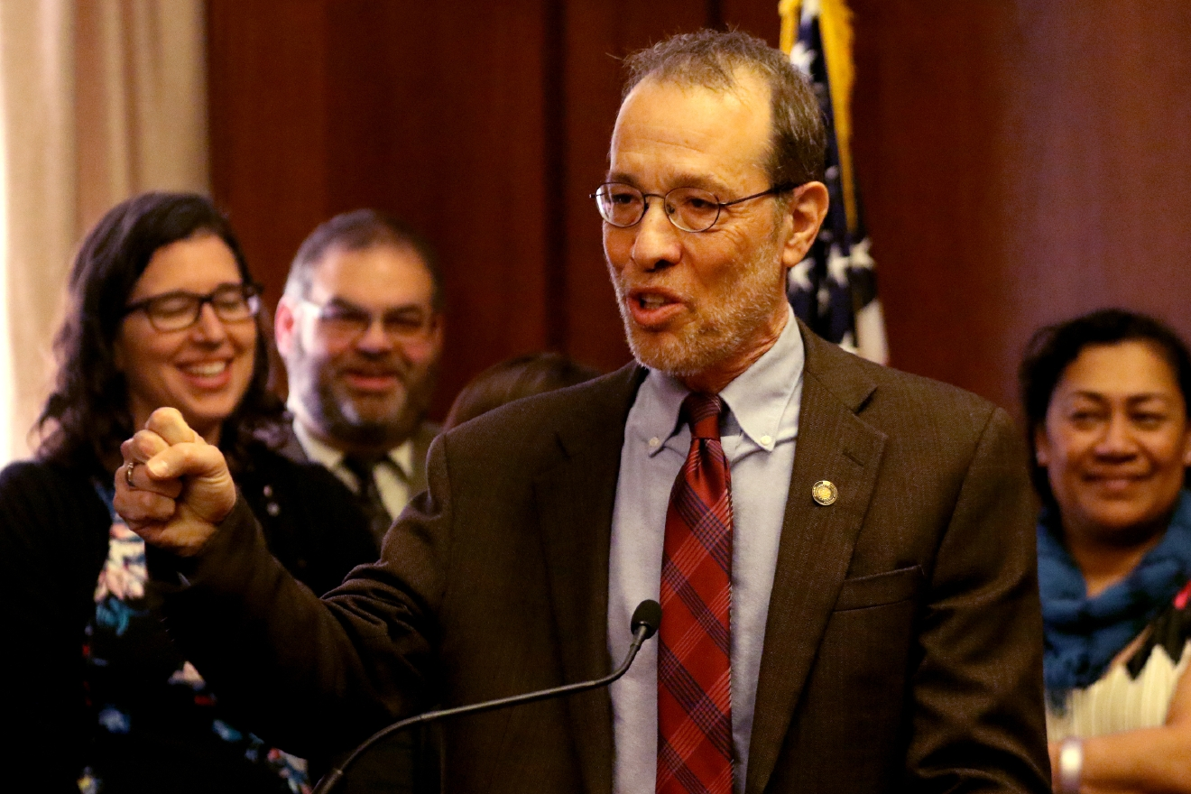 Sen. Michael Dembrow celebrates before Gov. Kate Brown signs Senate Bill 1532, increasing Oregon's minimum wage according to a tiered system, at the State Capitol in Salem on Wednesday, March 2, 2016. PortlandÂ?s minimum will rise to $14.75 by 2022, suburban areas to $13.50 and rural areas to $12.50. The tiered approach is based on economic factors.  (Anna Reed/Statesman-Journal via AP) MANDATORY CREDIT
