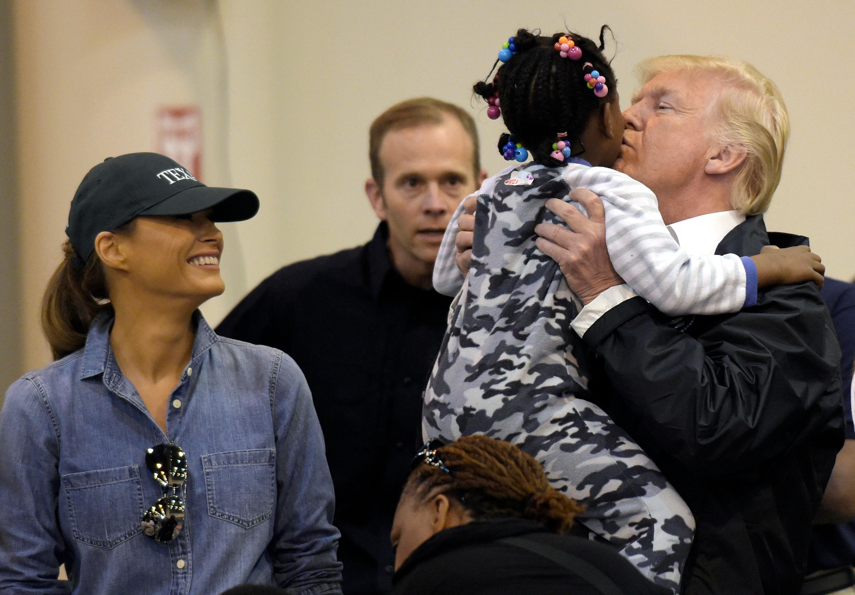 President Donald Trump and Melania Trump meet people impacted by Hurricane Harvey during a visit to the NRG Center in Houston, Saturday, Sept. 2, 2017.  He lifted this girl into his arms to give her a kiss.  It was his second trip to Texas in a week, and this time his first order of business was to meet with those affected by the record-setting rainfall and flooding. He's also set to survey some of the damage and head to Lake Charles, Louisiana, another hard-hit area. (AP Photo/Susan Walsh)