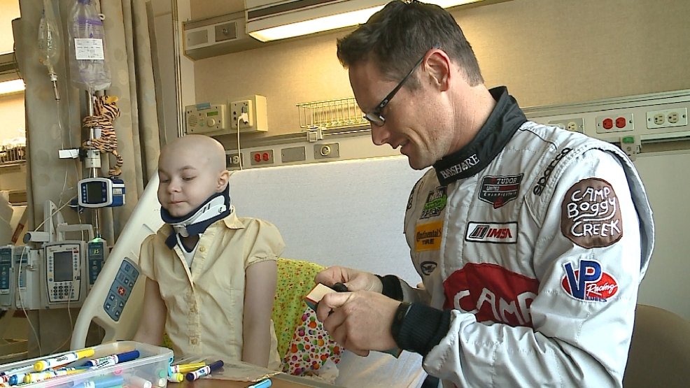 Gunnar Jeannette, a sports car driver, visits with eight-year-old Norah Derby at St. Vincent Hospital in Green Bay on Aug. 8, 2014. (WLUK)