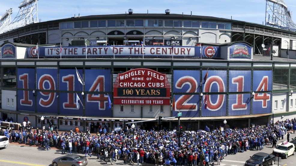 Baseball fans wait to enter Wrigley Field for the 100th anniversary of the first baseball game at the park, before a game between the Arizona Diamondbacks and Chicago Cubs, Wednesday, April 23, 2014, in Chicago. (AP Photo/Charles Rex Arbogast)