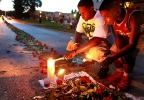 In this photo taken on Thursday, Aug. 21, 2014, Theo Murphy, left, of Florissant, Mo., and his brother Jordan Marshall, 11, light candles at a memorial on Canfield Drive in Ferguson, Mo., where where unarmed Michael Brown was fatally shot by Ferguson Police Officer Darren Wilson. A small group of people, who preferred to remain anonymous,laid roses along the middle of the road that stretched about 60 yards. (AP Photo/St. Louis Post-Dispatch, Christian Gooden)