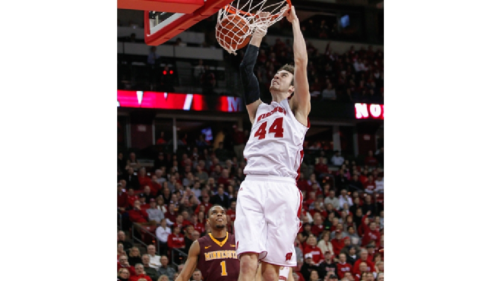 Wisconsin's Frank Kaminsky dunks over Minnesota's Andre Hollins during the second half of an NCAA college basketball game Thursday, Feb. 13, 2014, in Madison, Wis. Wisconsin beat Minnesota 78-70. (AP Photo/Andy Manis)