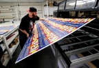"Josh Deinert, a graphic designer at Fast Signs, takes a sheet of anti-Senate Bill 1062 signs that read ""Open For Business To Everyone"" off the printer, Wednesday, Feb. 26, 2014 in Phoenix. (AP Photo/Matt York)"