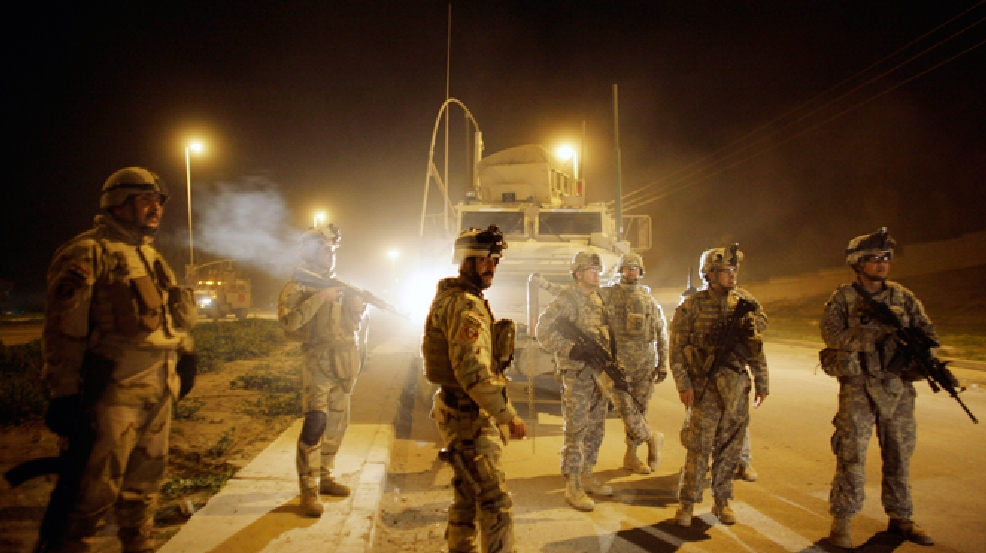 FILE - In this March 7, 2010 file photo, U.S. Army soldiers from B Troop, 3rd Squadron, 7th Cavalry Regiment and Iraqi Army soldiers watch comrades detain men suspected of planting a roadside bomb after polls closed for the national election in Mosul, north of Baghdad, Iraq. (AP Photo/Maya Alleruzzo, File)