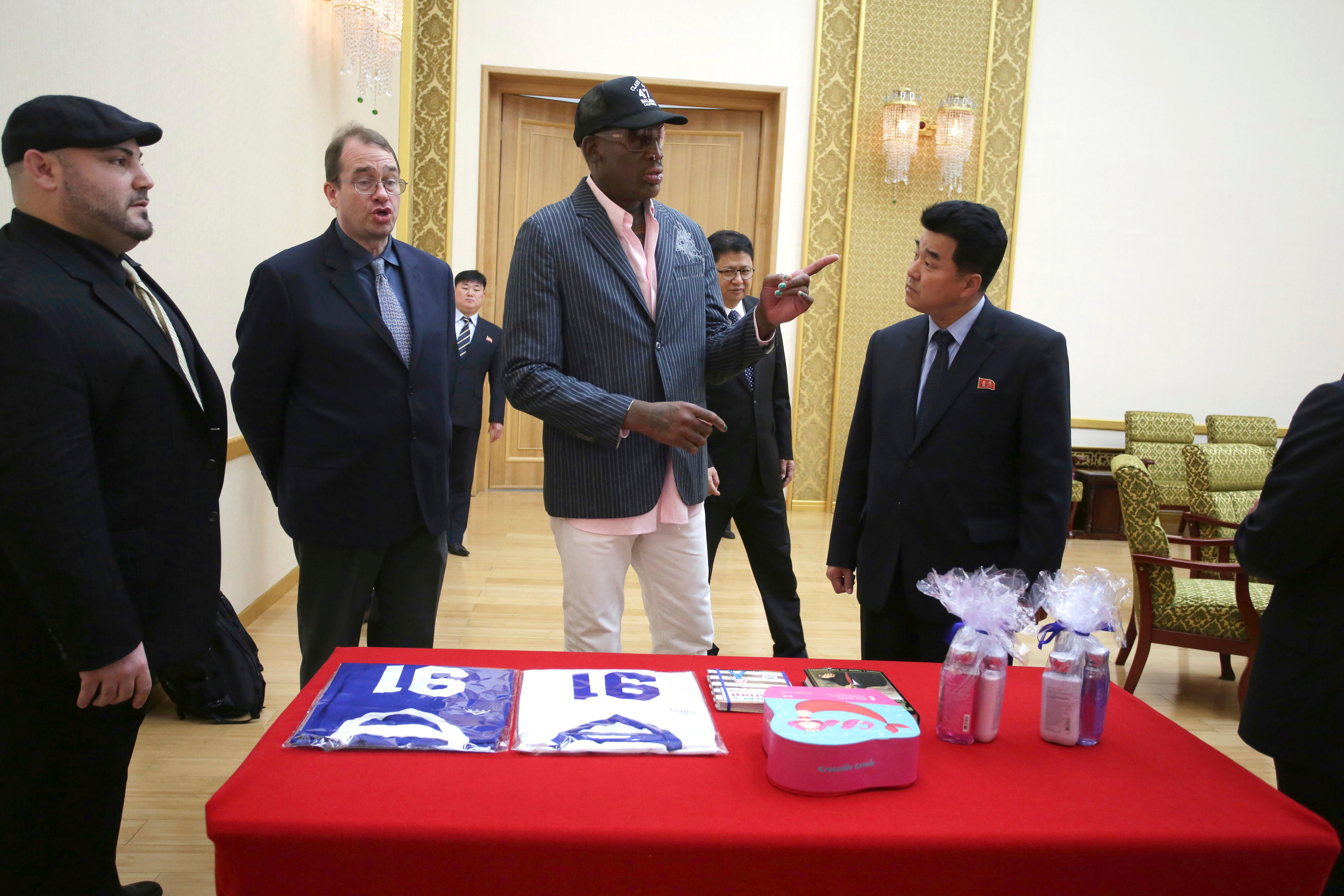 "Former NBA basketball star Dennis Rodman presents gifts comprising of autographed basketball jerseys, bath soaps and two books, titled ""Where's Waldo?"" and ""Trump The Art of the Deal"" to North Korea's Sports Minister Kim Il Guk, right, Thursday, June 15, 2017, in Pyongyang, North Korea. Standing on his left is Joseph Terwilliger, Columbia University academic. (AP Photo/Kim Kwang Hyon)"