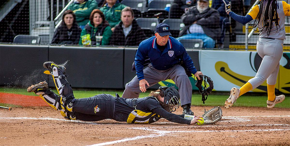 The Duck's catcher Gwen Svekis (#21) takes a dive for home base as The Golden Bears' Jazmyn Jackson (#24) scores a point. The Oregon Ducks defeated the Cal Golden Bears 2-1 in the second game of the three game series. Photo by August Frank, Oregon News Lab