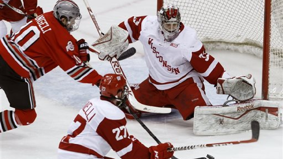 Wisconsin goalie Joel Rumpel, right, stops a shot by Ohio State forward Darik Angeli, top left, as Wisconsin defenseman Frankie Simonelli (27) watches during the third period of the championship college hockey game of the Big 10 Conference tournament in St. Paul, Minn., Saturday, March 22, 2014. Wisconsin won 5-4 in overtime. (AP Photo/Ann Heisenfelt)