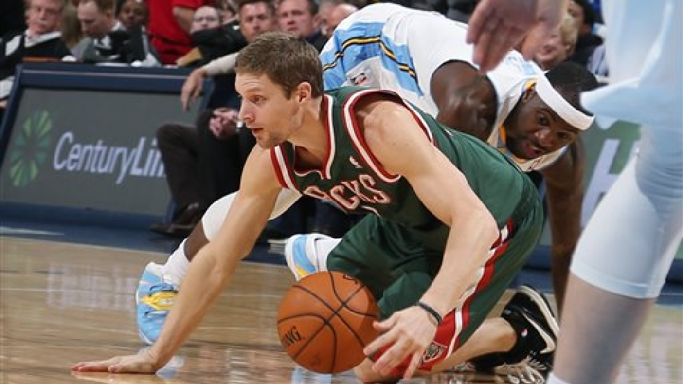 Milwaukee Bucks guard Luke Ridnour, front, picks up loose ball as Denver Nuggets guard Ty Lawson covers in the first quarter of an NBA basketball game in Denver, Wednesday, Feb. 5, 2014. (AP Photo/David Zalubowski)