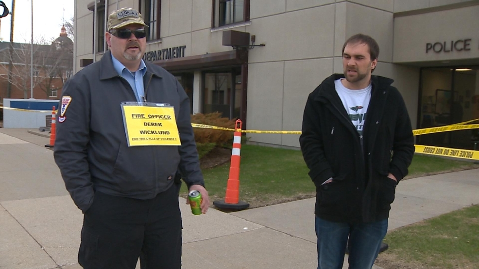 A handful of protesters demonstrate outside the Green Bay Police Department.