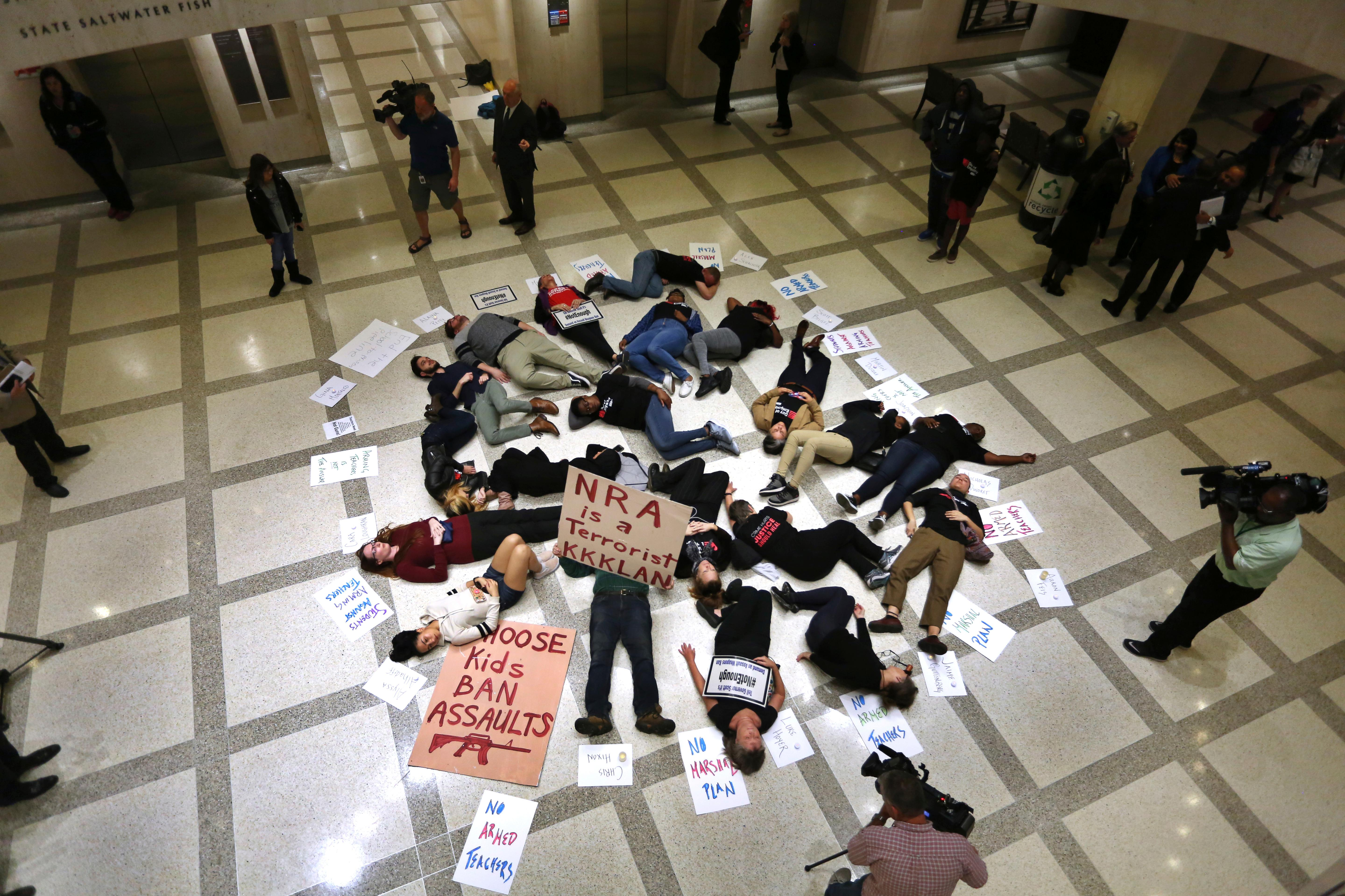 About 20 protesters participate in a die-In on the fourth floor rotunda of the Florida Capitol, in Tallahassee Tuesday, March 6, 2018, as they continue to push for an assault weapons ban. Lawmakers in the Florida House were debating a gun/school safety bill at the time. (Scott Keeler/The Tampa Bay Times via AP)