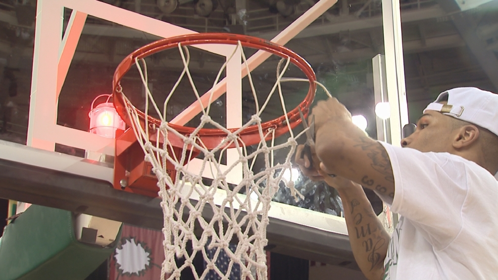 Keifer Sykes of the Green Bay Phoenix cuts down the net at the Resch Center following their win Thursday night.