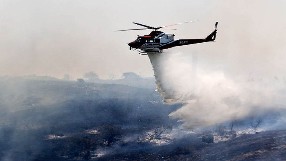 A helicopter attacks a wildfire burning in the north county of San Diego Tuesday, May 13, 2014, in San Diego. (AP Photo)