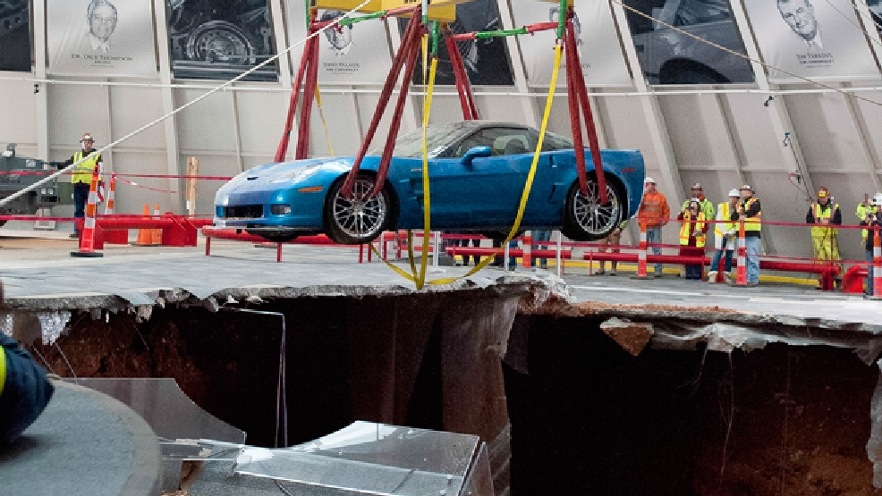 One of eight Chevrolet Corvettes is removed from a sinkhole in the Skydome at the National Corvette Museum, Monday, March. 3, 2014, in Bowling Green, Ky. On Feb. 12, a large sinkhole swallowed eight prized cars like they were toys, piling them in a heap amid loose dirt and concrete fragments. (AP Photo/Daily News, Alex Slitz)
