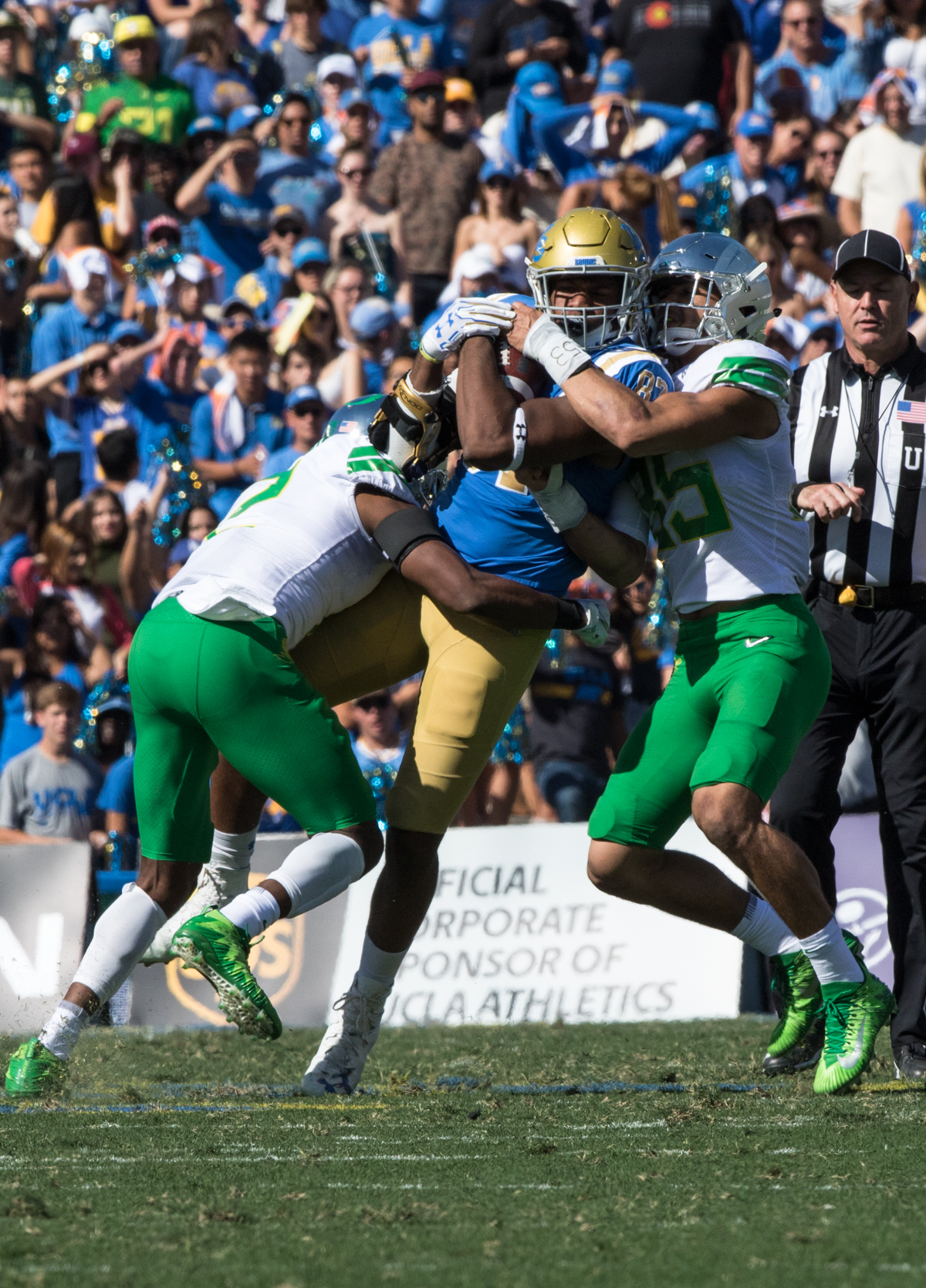 UCLA tight end Jordan Wilson (#87) is dragged down by two Oregon defenders. The Oregon Ducks rallied during the second quarter to go into halftime tied 14-14 with the UCLA Bruins at Rose Bowl Stadium in Pasadena, California. Photo by Austin Hicks, Oregon News Lab