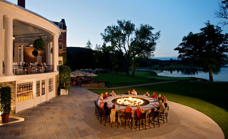 When it's time to eat, choose from casual patio dining, fine dining inside, or perhaps sitting around the fire bar. All offer panoramic sunset views on the lake.{ } (Image: Courtesy The Otesaga Resort)