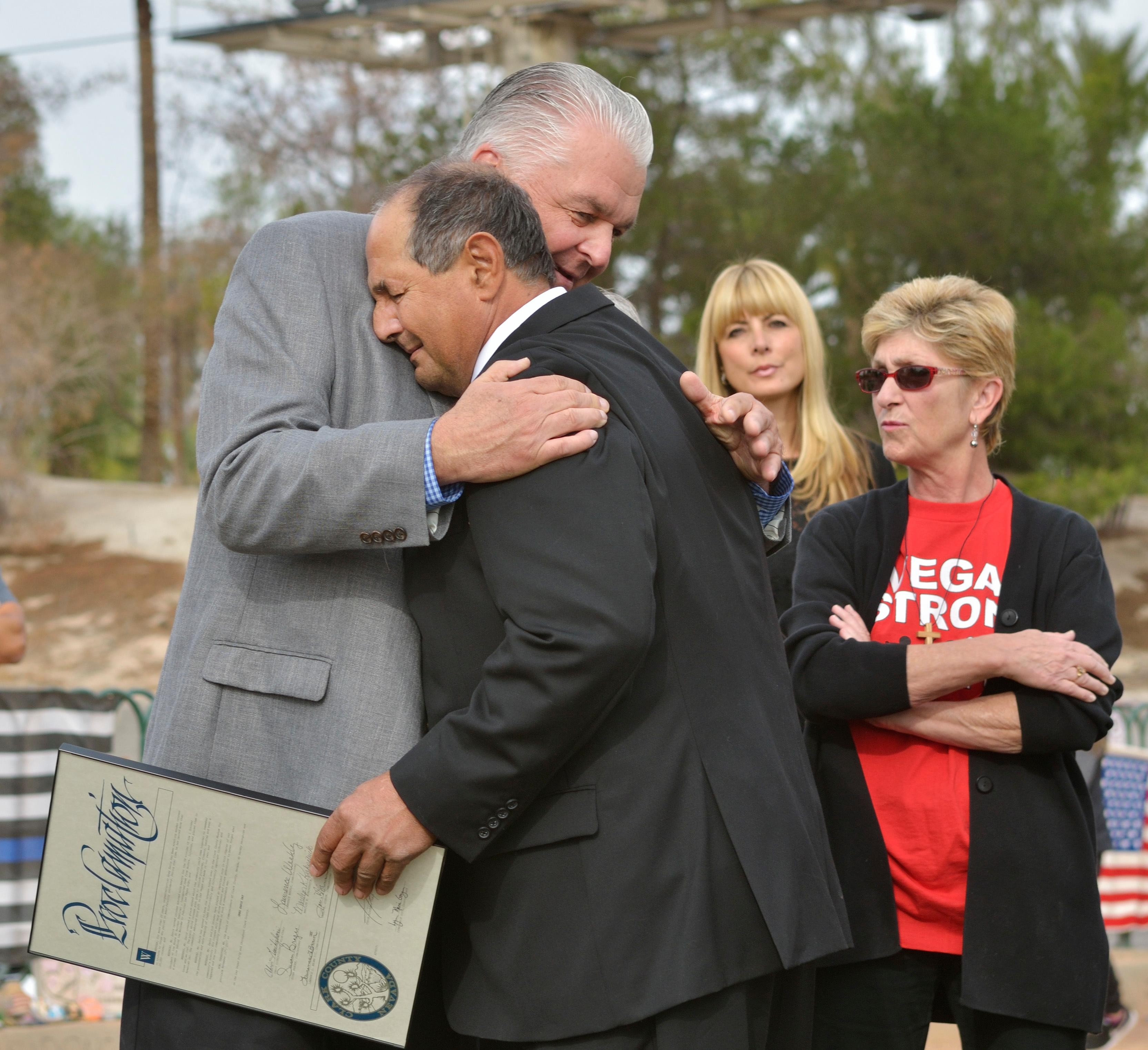 "Greg Zanis, in dark suit, gets a hug from Clark County Commissioner Steve Sisolak during ""Greg Zanis Day"" at the Welcome to Fabulous Las Vegas sign on the Las Vegas Strip on Sunday, Nov. 12, 2017. Zanis, a carpenter from Aurora, Ill., was recognized by the Clark County Commision for creating 58 crosses memorializing those who died during the Route 91 Harvest festival shooting on Oct. 1. The crosses were later moved to the Clark County Museum for its permanent collection. [Bill Hughes/Las Vegas News Bureau]"