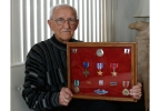 March 24, 2014, James Krucas sits for a photo at his home in Racine as he holds a display of medals he earned during his service in World War II. Krucas is one of the few remaining veterans of the D-Day invasion in Europe. (AP Photo/M.L. Johnson)