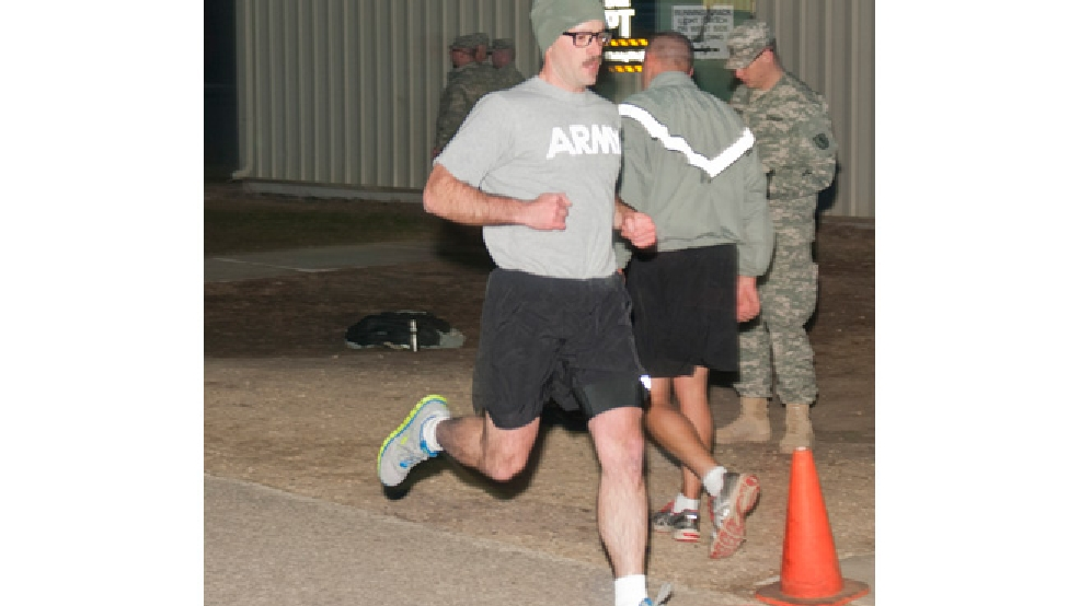 Spc. Zackary Warnke with the 32nd Infantry Brigade Combat Team, crosses the finish line in the two-mile run event during the Army Physical Fitness Test during the 2014 State Best Warrior Competition at Fort McCoy, April 11, 2014. (Mobile Public Affairs Detachment photo by Staff Sgt. Megan Leuck)