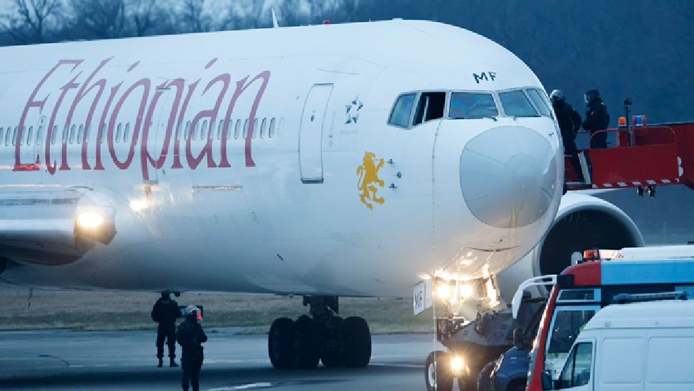 Police stand around the aircraft after passengers were evacuated from a hijacked Ethiopian Airlines Plane on the airport in Geneva, Switzerland, Monday, Feb. 17, 2014. A hijacked aircraft traveling from Addis Abeda, Ethiopia, to Rome, Italy, has landed at Geneva's international airport early Monday morning. Swiss authorities have arrested the hijacker. (AP Photo/Keystone, Salvatore Di Nolfi)