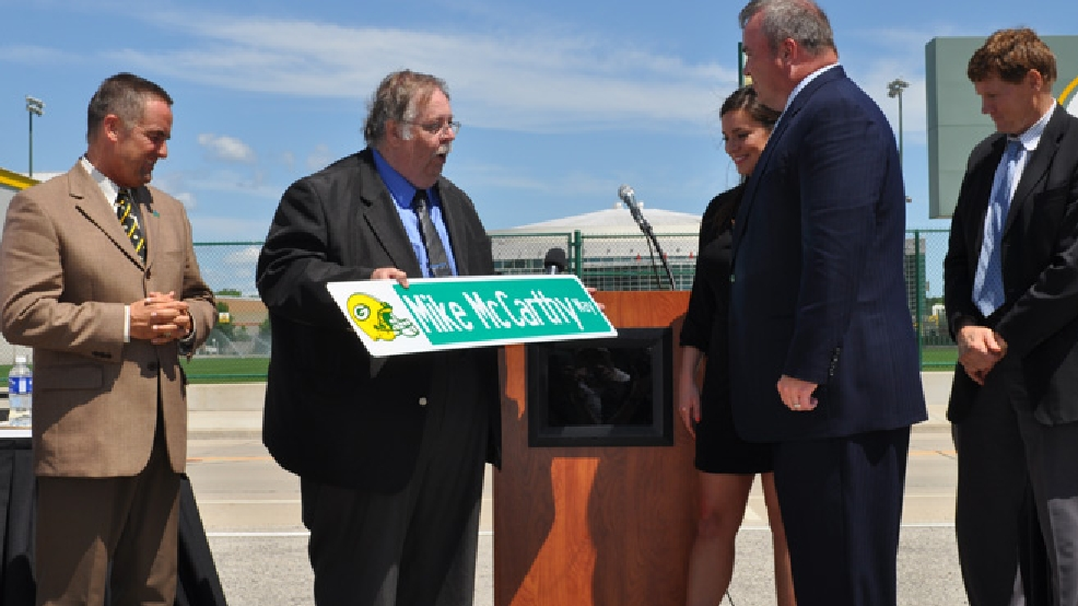Ashwaubenon Village President Mike Aubinger presents Green Bay Packers head coach Mike McCarthy with a souvenir Mike McCarthy Way street sign, July 23, 2014. (WLUK/Brooke Zauner)