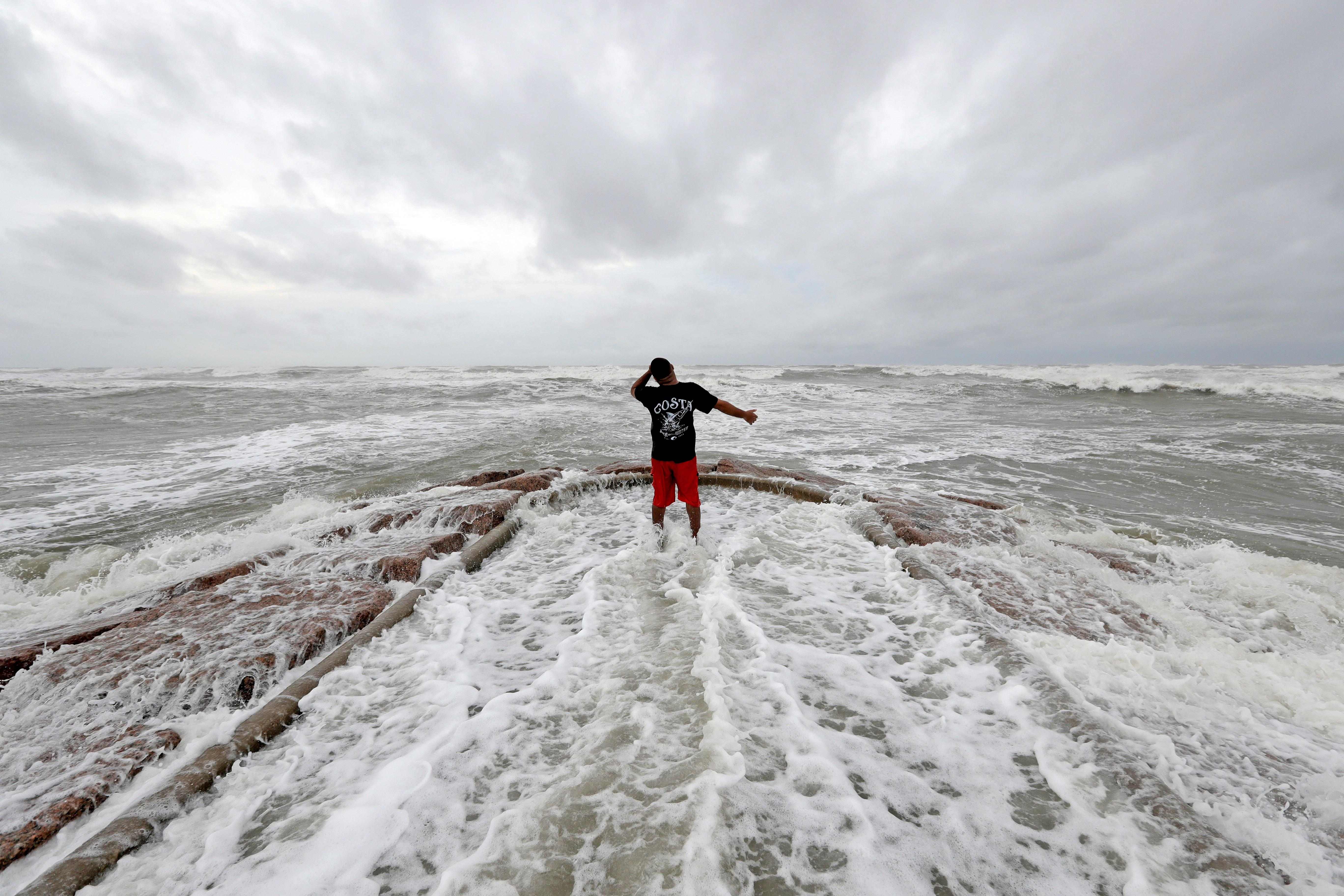 Luis Perez watches waves crash again a jetty in Galveston, Texas as Hurricane Harvey intensifies in the Gulf of Mexico Friday, Aug. 25, 2017. Harvey is forecast to be a major hurricane when it makes landfall along the middle Texas coastline. (AP Photo/David J. Phillip)