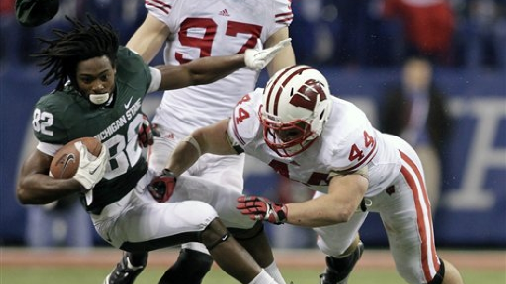 Michigan State's Keshawn Martin loses his helmet as he is tackled by Wisconsin's Chris Borland during the second half of the Big Ten Conference championship NCAA college football game on Saturday, Dec. 3, 2011, in Indianapolis. (AP Photo/AJ Mast)