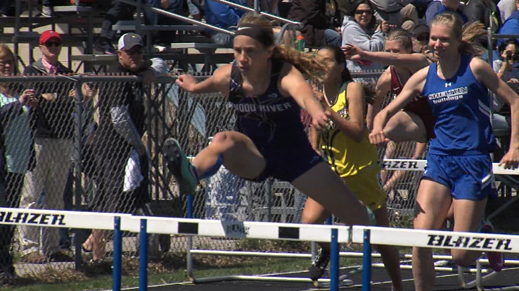 Emily Loy (left) of Wood River clears the final hurdle to win the 100 meter hurdles at the Ron Priebe Invite in Gibbon, April 20, 2017 (NTV News)