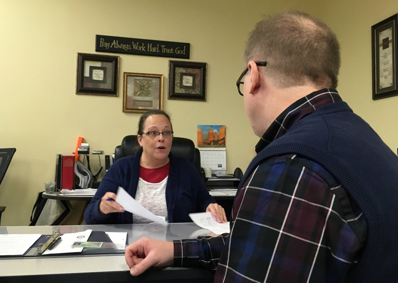 David Ermold, right, speaks with Clerk Kim Davis as he files to run for Rowan County Clerk Wednesday, Dec. 6, 2017, in Morehead, Ky.{&amp;nbsp;}Davis denied Ermold and his husband a marriage license two years ago because she was opposed to gay marriage for religious reasons. (AP Photo/Adam Beam) <p></p>