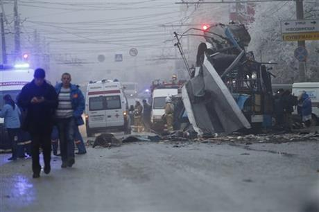 Ambulances line up a site of a trolleybus explosion, background, in Volgograd, Russia Monday, Dec. 30, 2013. A bomb blast tore through the trolleybus in the city Volgograd on Monday morning, killing at least 10 people.