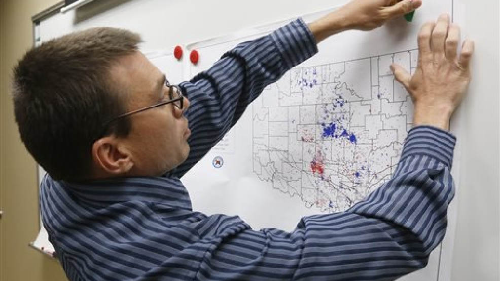 In this June 26, 2014 file photo, Austin Holland, research seismologist at the Oklahoma Geological Survey, hangs up a chart depicting earthquake activity at their offices at the University of Oklahoma in Norman, Okla. States where hydraulic fracturing is taking place have seen a surge in seismic activity, raising suspicions that the unconventional drilling method, especially the wells in which the industry disposes of its wastewater, could be to blame. (AP Photo/Sue Ogrocki, File)
