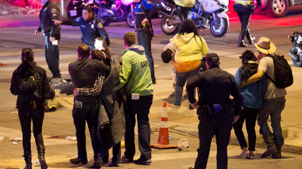 People walk away after a fatal crash on Red River Street in downtown Austin, Texas on Wednesday March 12, 2014. (AP Photo/Austin American-Statesman, Jay Janner)