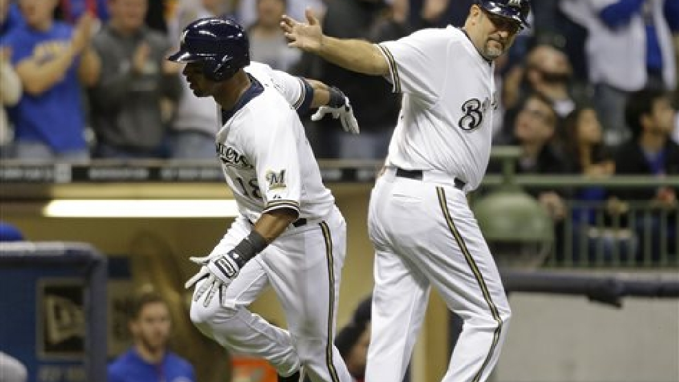 Milwaukee Brewers' Khris Davis, left, rounds the bases as third base coach Ed Sedar looks on after hitting a home run against the Chicago Cubs during the sixth inning of a baseball game on Saturday, April 26, 2014, in Milwaukee. (AP Photo/Jeffrey Phelps)