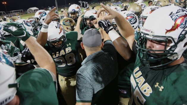 Bill Clark huddles with the victorious Green team during UAB's Green and Gold Game on Oct. 26. The Blazers return to action for real this year after being shuttered in 2015-16. (Photo courtesy UAB Athletics)