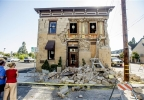 Pedestrians stop to examine a crumbling facade at the Vintner's Collective tasting room in Napa, Calif., following an earthquake Sunday, Aug. 24, 2014. Officials in the city of Napa say 15 to 16 buildings are no longer inhabitable after Sunday's magnitude-6.0 earthquake, and there is only limited access to numerous other structures. (AP Photo/Noah Berger)