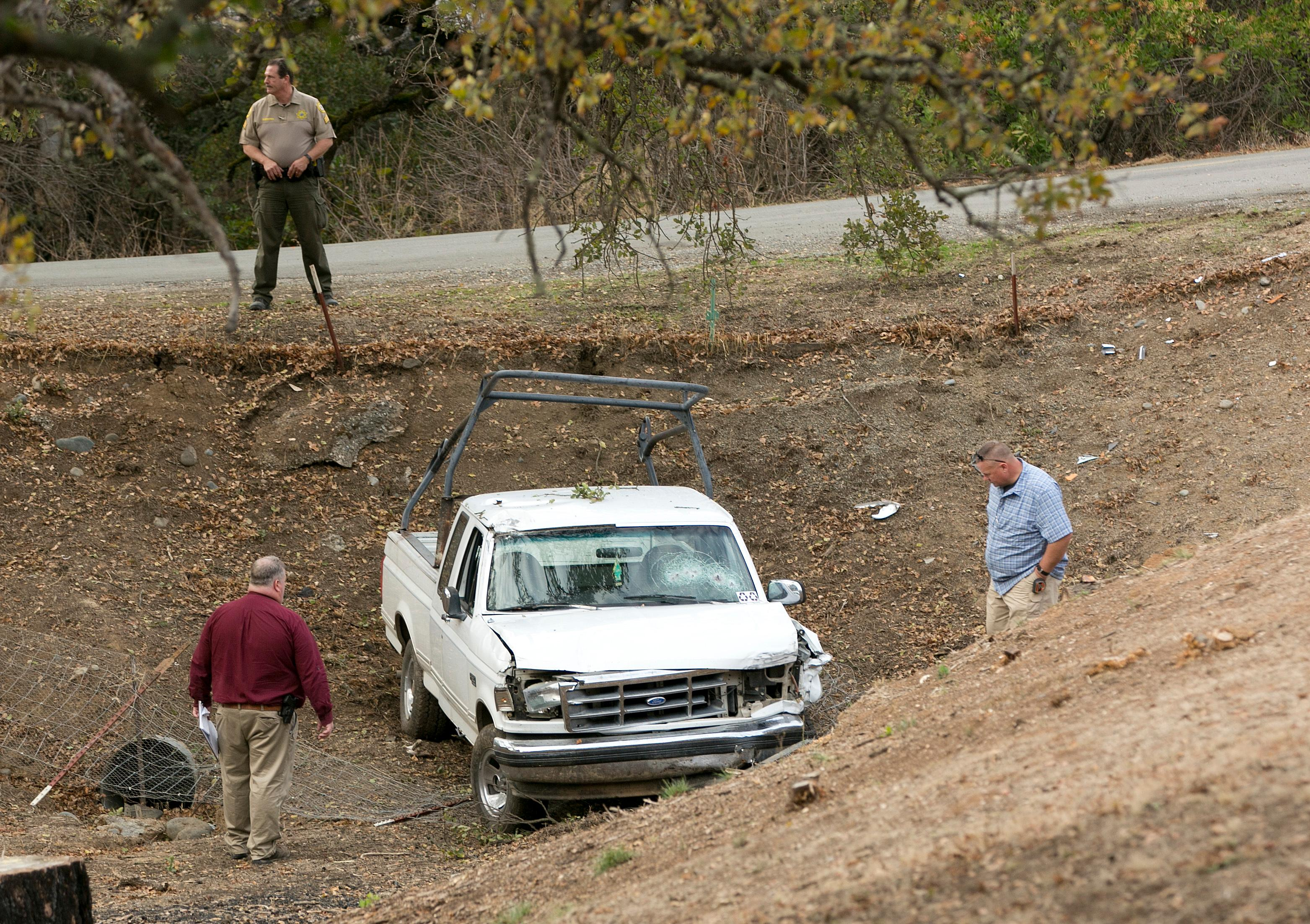 "Investigators view a pickup truck involved in a deadly shooting rampage at the Rancho Tehama Reserve, near Corning, Calif., Tuesday, Nov. 14, 2017. A gunman driving stolen vehicles and choosing his targets at random opened fire ""without provocation"" in the tiny, rural Northern California town Tuesday, killing several people, including a student at an elementary school, before police shot him dead, authorities said. (AP Photo/Rich Pedroncelli)"
