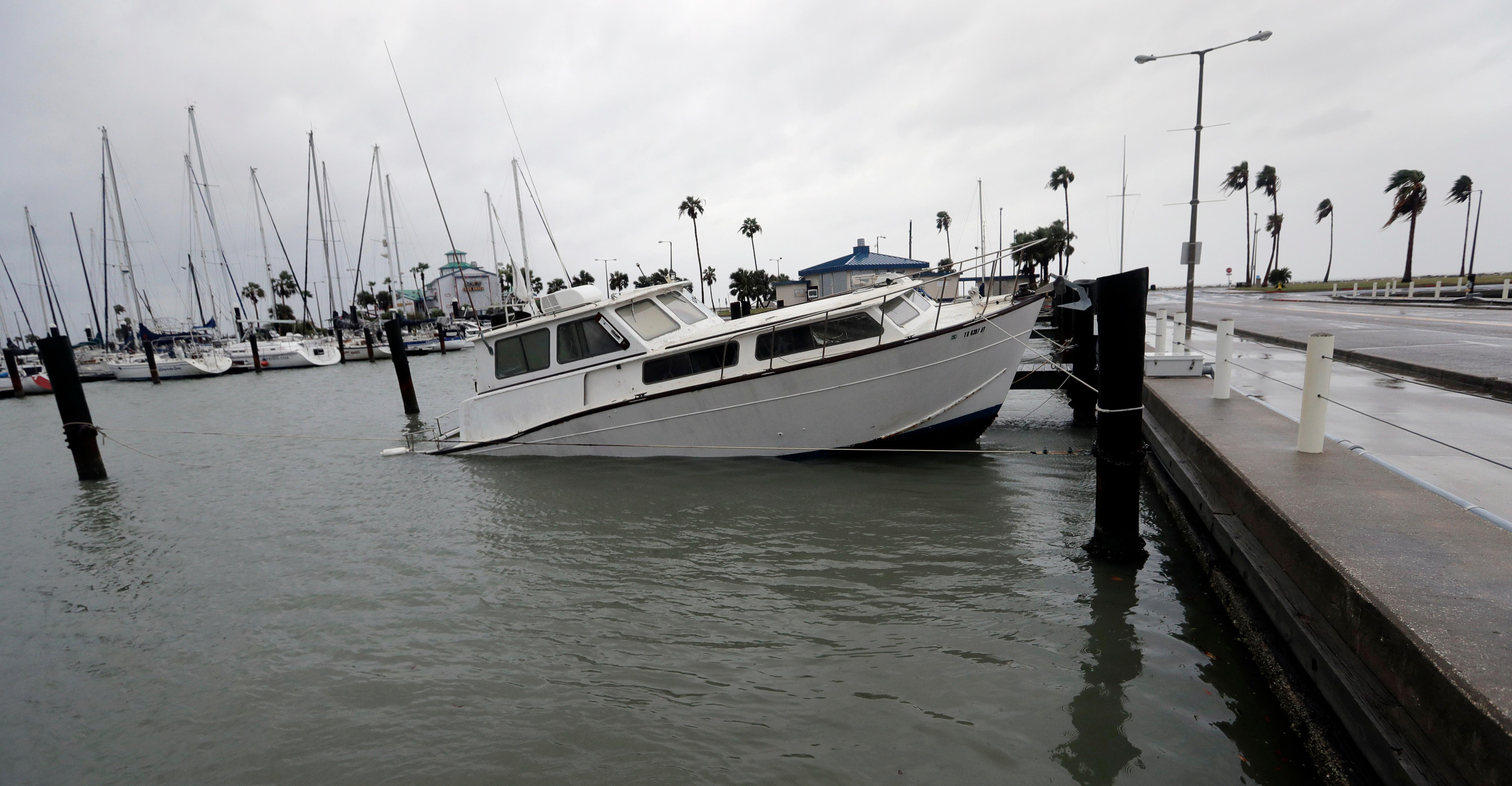 A fishing boat is left partial submerged after Hurricane Harvey swept through the area, Saturday, Aug. 26, 2017, in Corpus Christi, Texas. Harvey has been further downgraded to a Category 1 hurricane as it churns slowly inland from the Texas Gulf Coast, already depositing more than 9 inches of rain in South Texas. (AP Photo/Eric Gay)