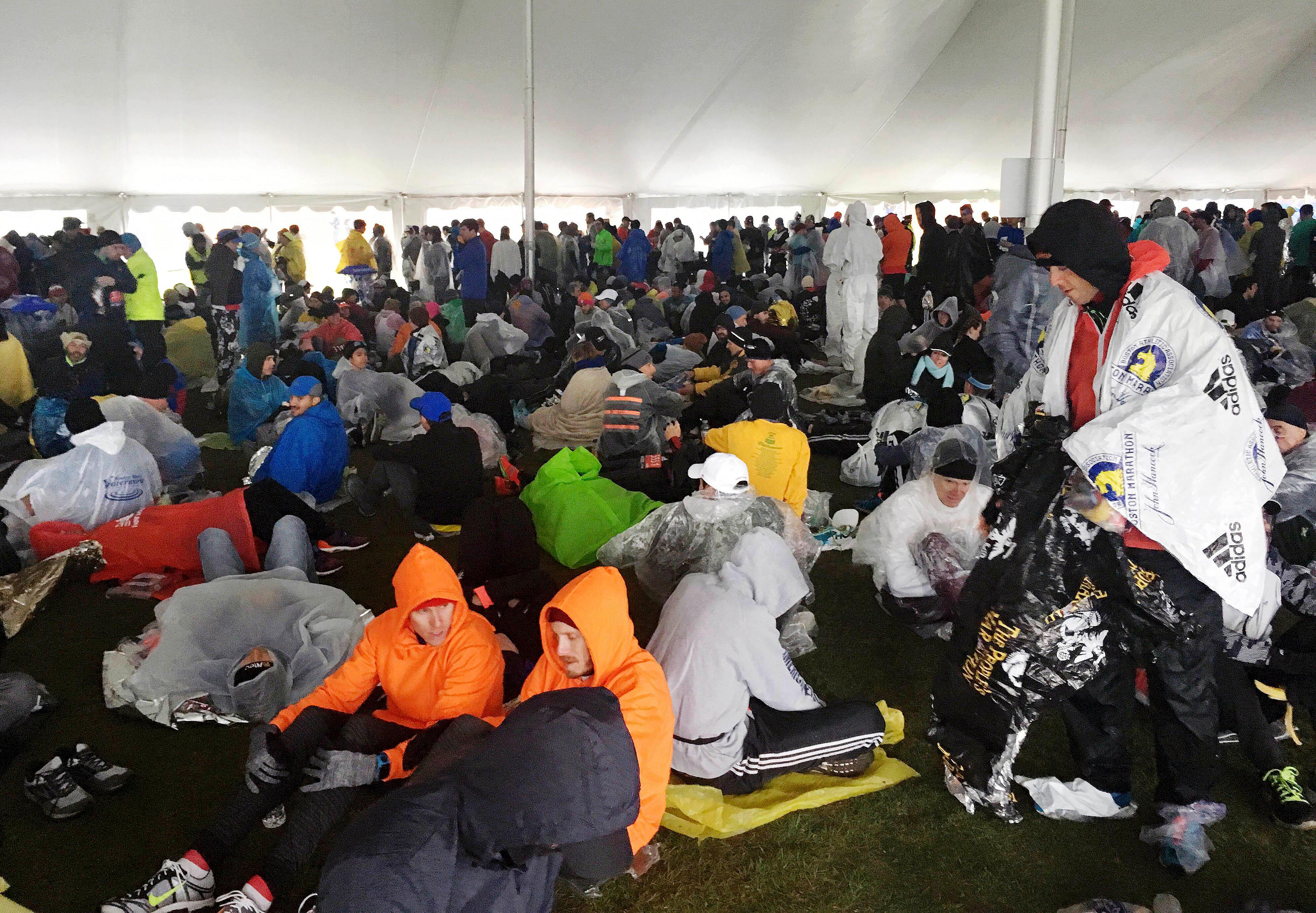 Athletes wait under a tent at the athlete's village for the start of the the 122nd Boston Marathon on Monday, April 16, 2018, in Hopkinton, Mass. (AP Photo/Jennifer McDermott)
