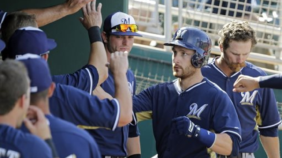 Milwaukee Brewers' Jonathan Lucroy celebrates in the dugout after a solo home run off Cincinnati Reds relief pitcher Pedro Beato in the seventh inning of a spring exhibition baseball game March 23, 2014, in Goodyear, Ariz. (AP Photo/Mark Duncan)