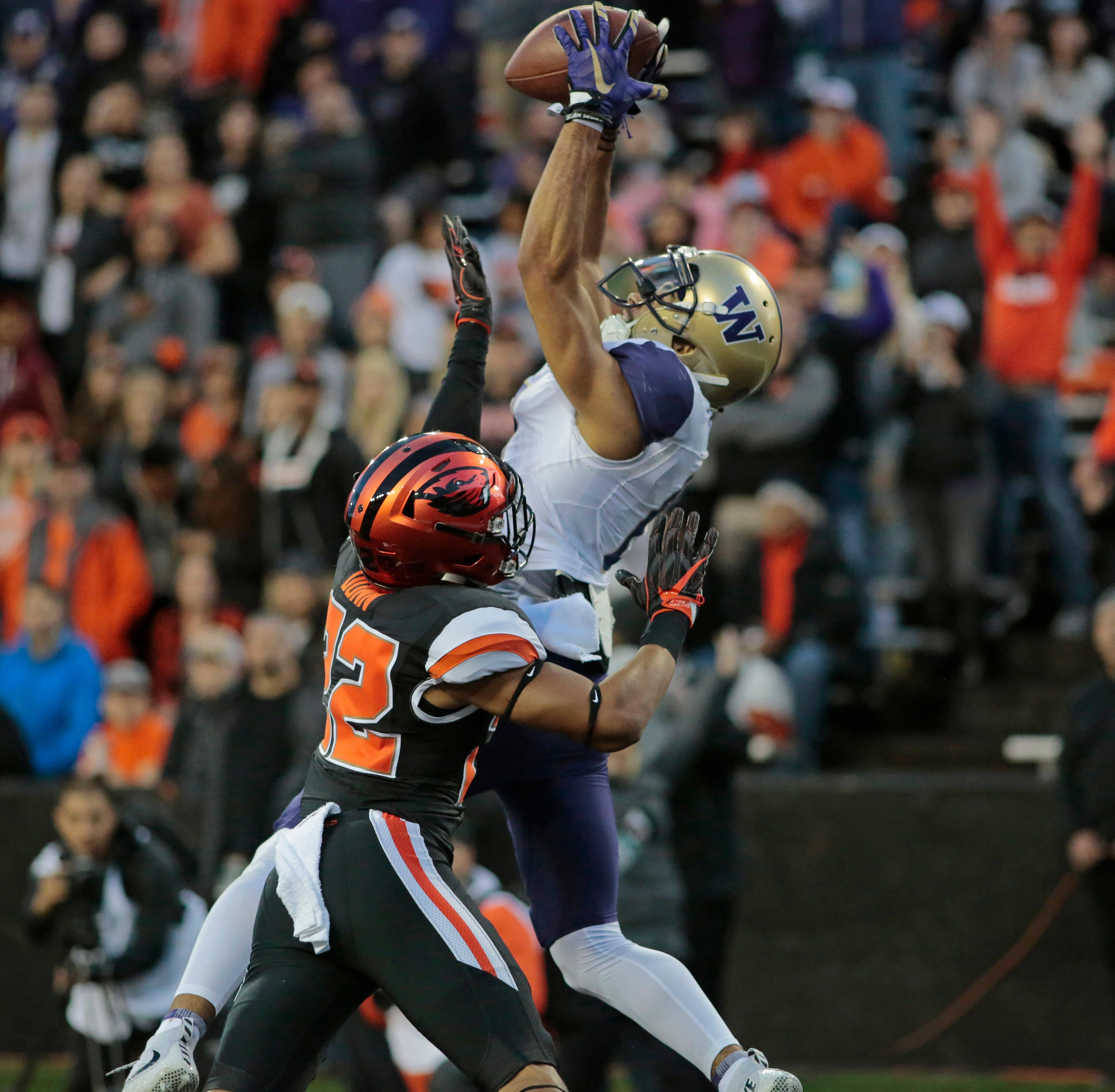 Washington wide receiver Dante Pettis (8) goes high over Oregon State's Isaiah Dunn (22) for a touchdown in the second half of an NCAA college football game, in Corvallis, Ore., Saturday, Sept. 30, 2017. Washington won 42-7. (AP Photo/Timothy J. Gonzalez)