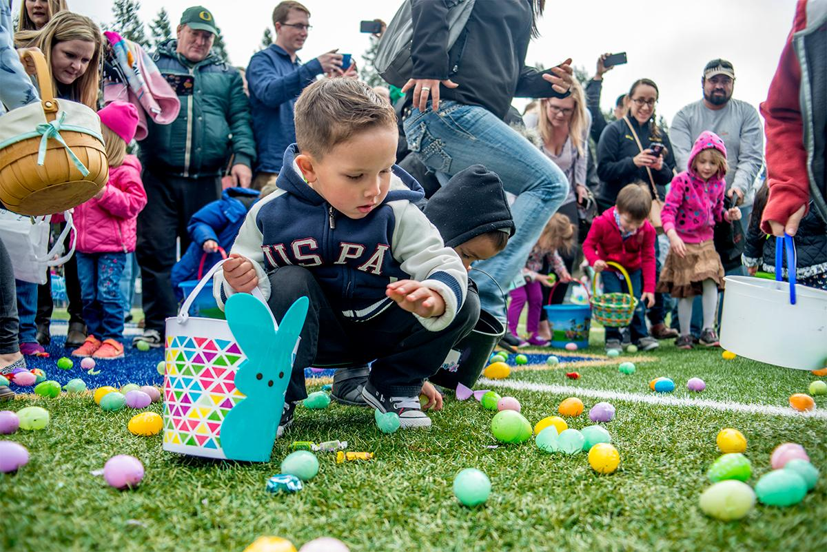 Hundreds of kids from young babies to school age converged on Marist High School on Saturday for a helicopter Easter egg drop. The event, put on by Joy Church, loaded up a large bucket with eggs then dropped it across the Marist football field by helicopter. Photo by Rhianna Gelhart, Oregon News Lab