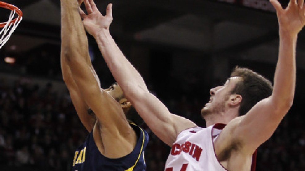 Michigan's Jon Horford, left, pulls down a defensive rebound away from Wisconsin's Frank Kaminsky during the second half of an NCAA college basketball game Saturday, Jan. 18, 2014, in Madison, Wis. Michigan defeated Wisconsin 77-70.