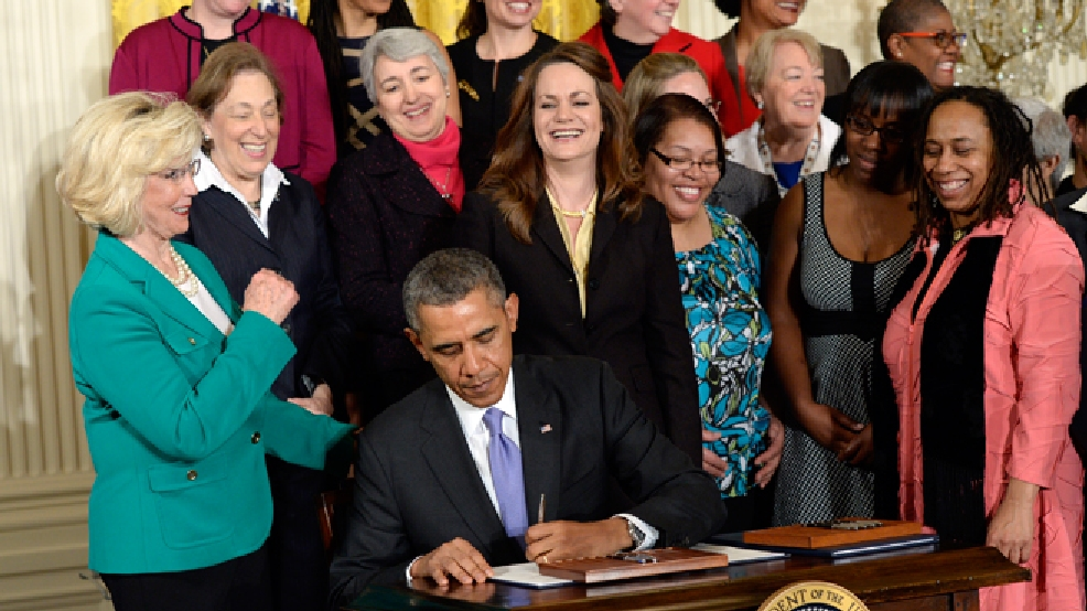 President Barack Obama signs executive actions, with pending Senate legislation, aimed at closing a compensation gender gap that favors men, Tuesday, April 8, 2014, in the East Room of the White House in Washington, during an event marking Equal Pay Day. Obama announced new executive actions to strengthen enforcement of equal pay laws for women. The president and his Democratic allies in Congress are making a concerted election-year push to draw attention to women's wages. Lilly Ledbetter, in green, watches at left. (AP Photo/Susan Walsh)