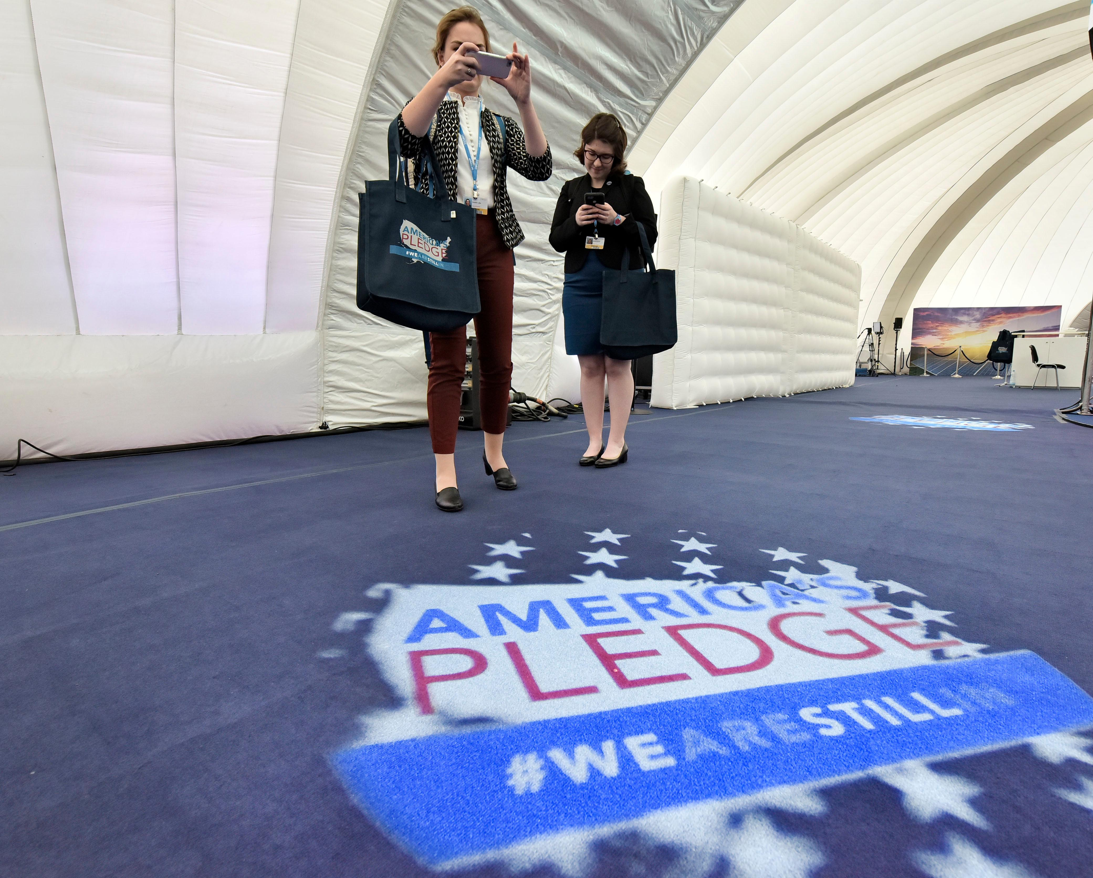 "Visitors make pictures inside the U.S. Climate Action Center at the COP 23 Fiji UN Climate Change Conference in Bonn, Germany, Thursday, Nov. 9, 2017. The non government movement ""We are still in"" established the pavilion and forum where dozens of American leaders will convene throughout the negotiations. (AP Photo/Martin Meissner)"
