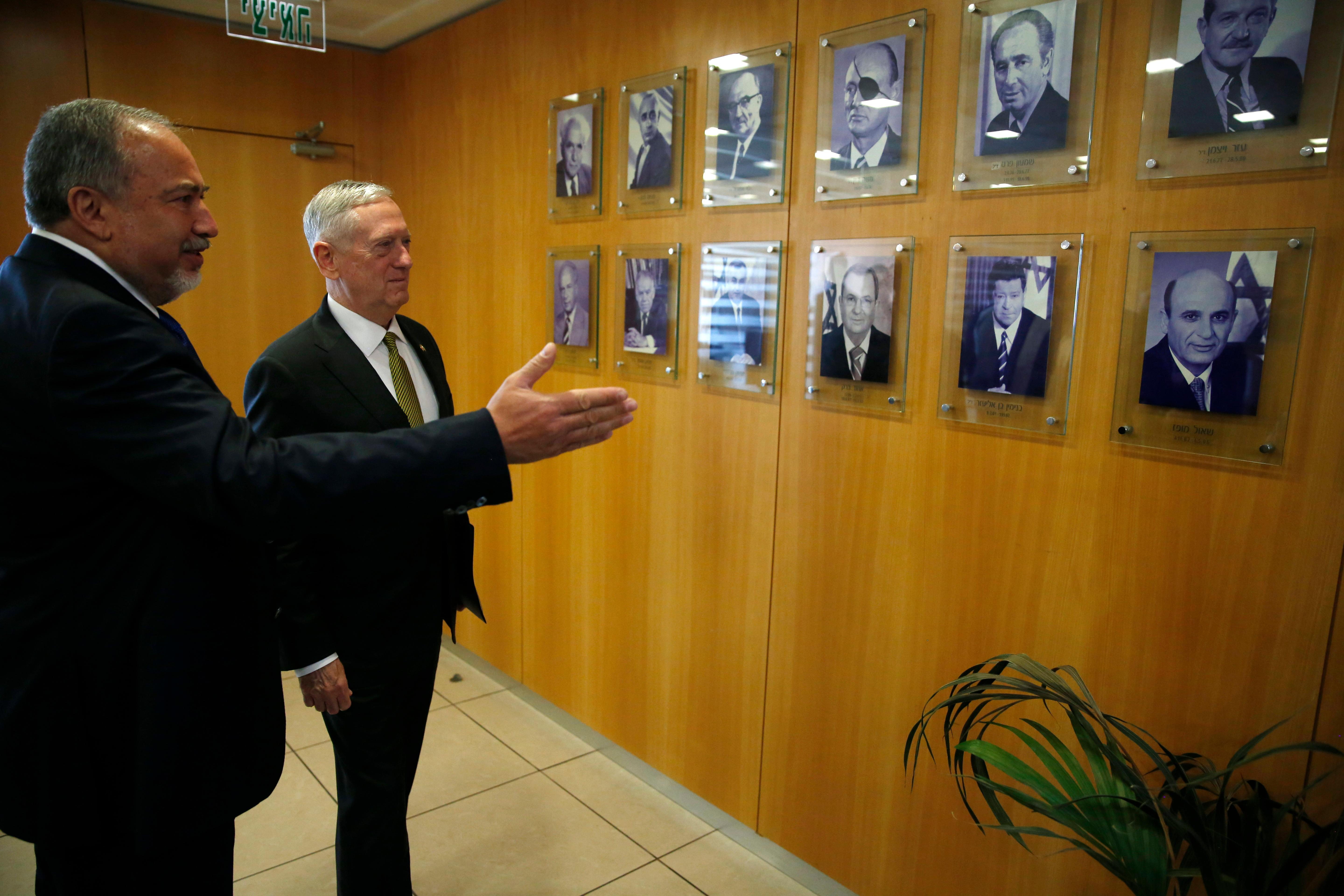 Israeli Defense Minister Avigdor Lieberman, left, shows U.S. Defense Secretary Jim Mattis pictures of his predecessors before they take their seats for a meeting in his office at the Defense Ministry in Tel Aviv, Israel, Friday, April 21, 2017. (Jonathan Ernst/Pool Photo via AP)