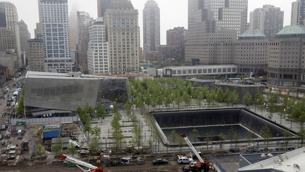 The pavilion entrance to the National September 11 Memorial Museum, left, is next to one of the memorial reflecting pools, right, at the World Trade Center, Thursday, May 15, 2014 in New York. (AP Photo/Mark Lennihan)