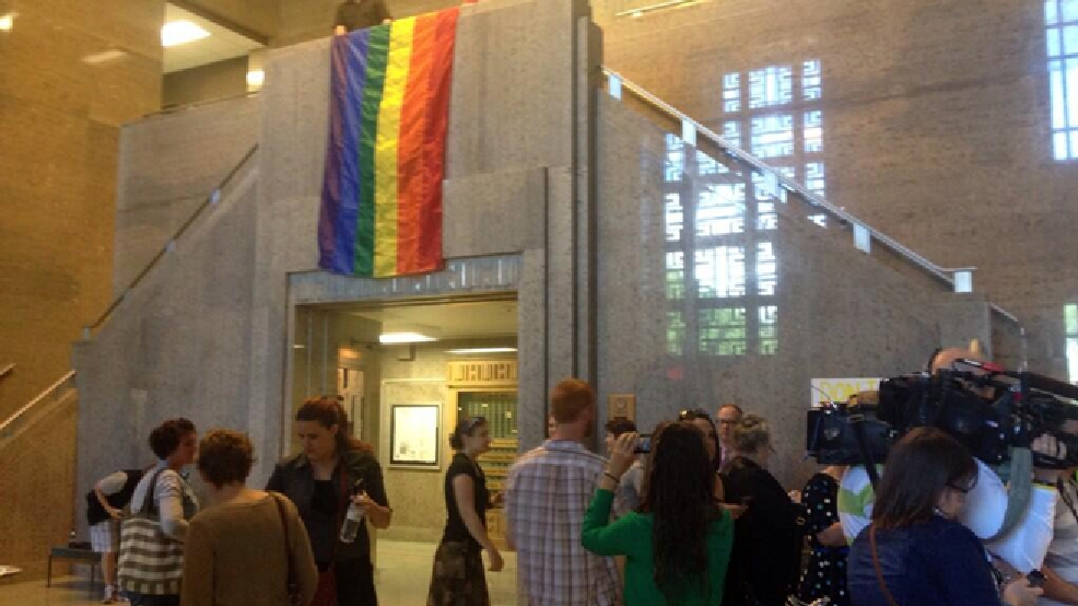 A rainbow flag is unfurled at the Outagamie County Administration Building June 9, 2014, as same-sex couples are allowed to begin filing paperwork for marriages. (WLUK/Bill Miston)