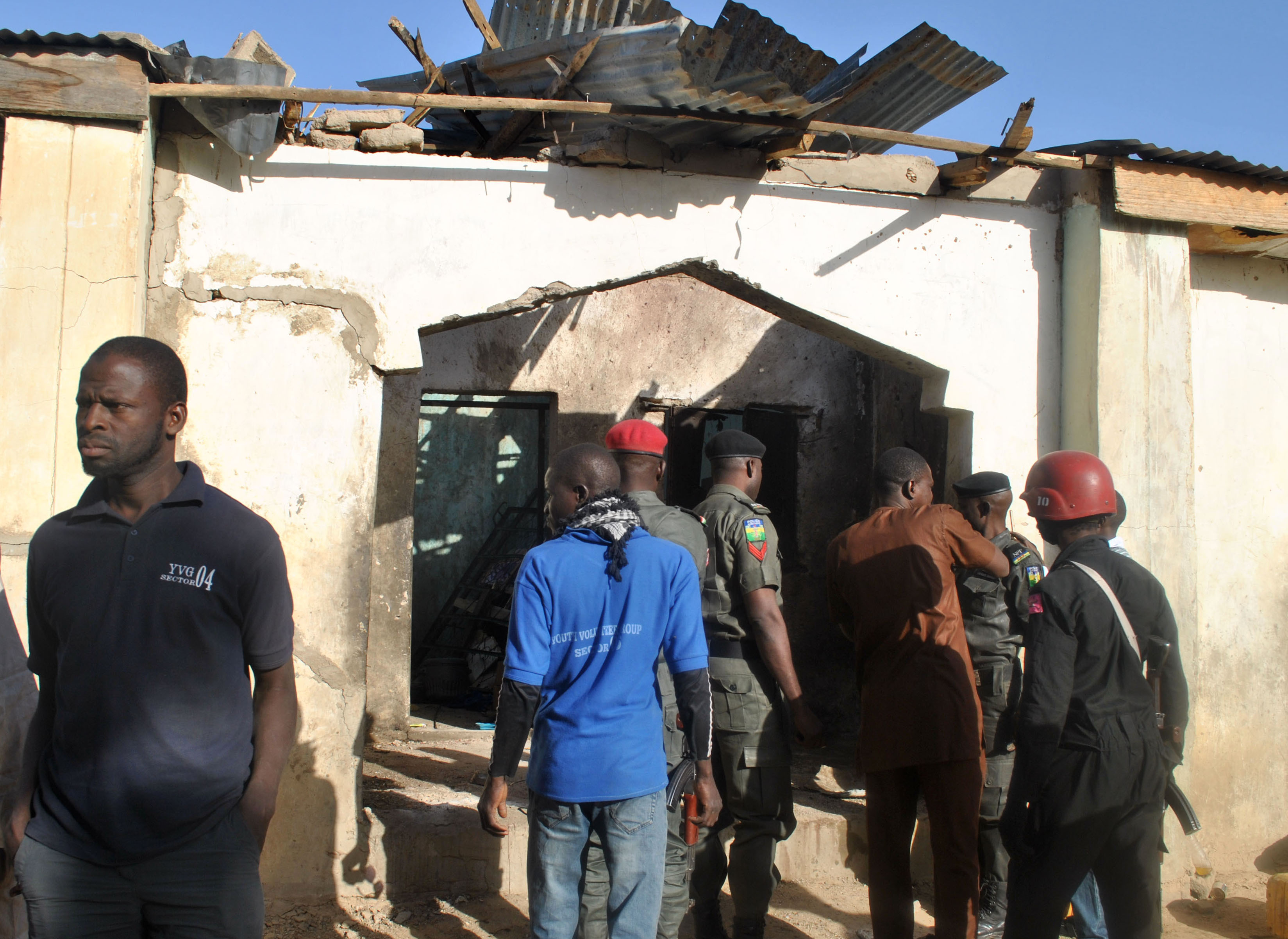 People gather at a damaged building following an attack by Boko Haram in Maiduguri, Nigeria Monday, Dec. 28, 2015. Boko Haram Islamic extremists struck the northeastern Nigerian city of Maiduguri for the first time in months Monday with rocket-propelled grenades and multiple suicide bombers, witnesses said. At least 50 people were killed and the death toll could go higher. (AP Photo/Jossy Ola)