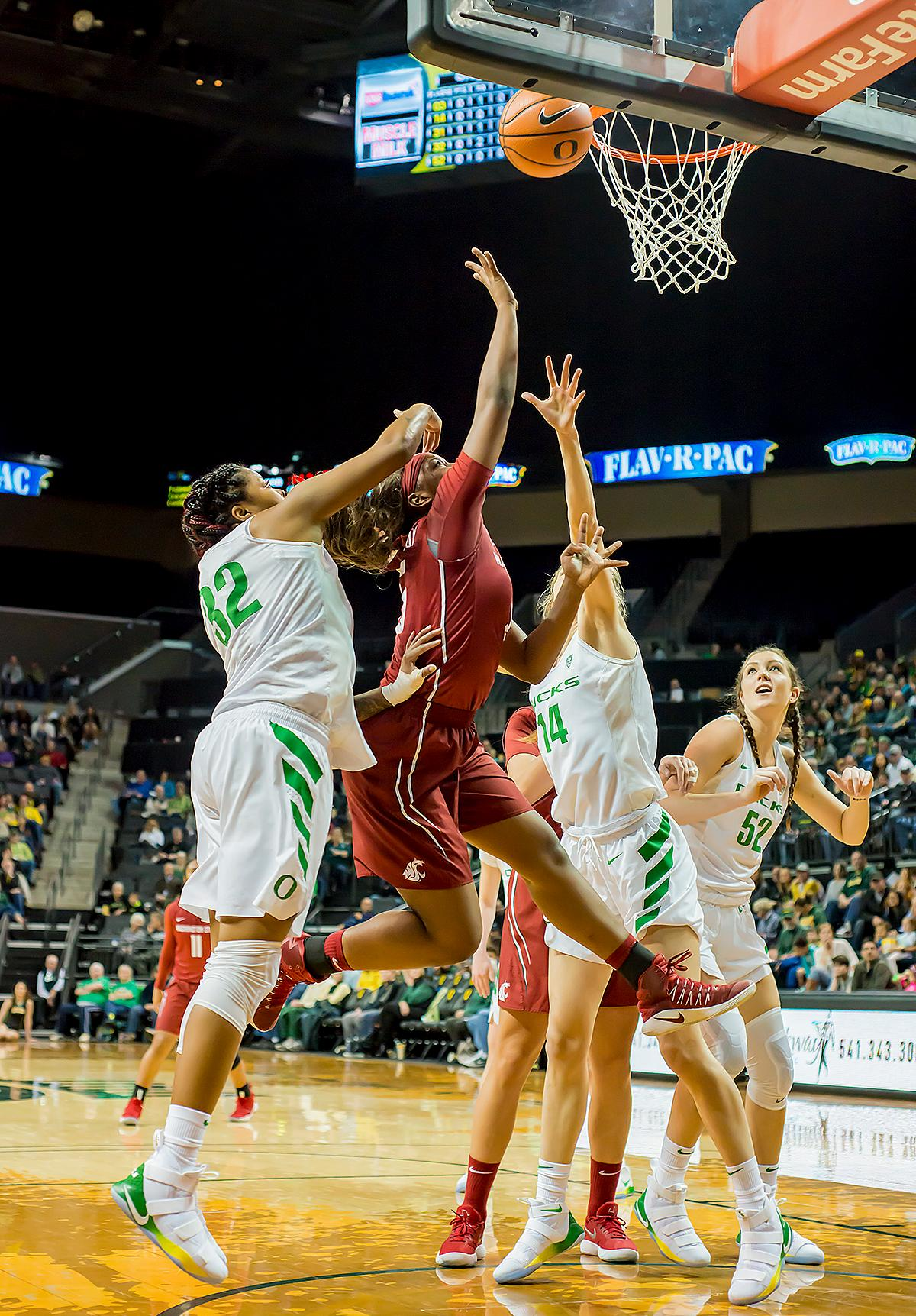 Washington State University Cougars Kayla Washington (#5, red jersey) fights for a rebound against Oregon Ducks Oti Gildon (#32), Lydia Giomi (#14) and Sierra Campisano (#52). In their first conference basketball game of the season, the Oregon Women Ducks defeated the Washington State Cougars 89-56 in Matt Knight Arena Saturday afternoon. Oregon's Ruthy Hebard ran up 25 points with 10 rebounds. Sabrina Ionescu shot 25 points with five three-pointers and three rebounds. Lexi Bando added 18 points, with four three-pointers and pulled down three rebounds. Satou Sabally ended the game with 14 points with one three-pointer and two rebounds. The Ducks are now 12-2 overall with 1-0 in conference and the Cougars stand at 7-6 overall and 0-1 in conference play. The Oregon Women Ducks next play the University of Washington Huskies at 1:00 pm on Sunday. Photo by Karly DeWees, Oregon News Lab